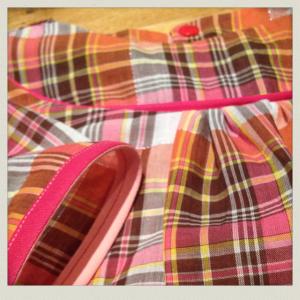 Détail de la blouse avec un biais bicolore fuchsia/rose.